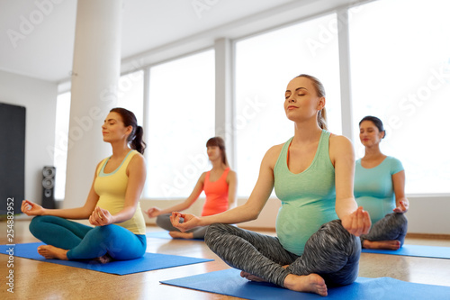 Leinwandbild Motiv pregnancy, fitness, people and healthy lifestyle concept - group of happy pregnant women meditating in lotus pose at gym yoga