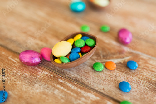 mata magnetyczna easter, sweets and confectionery concept - close up of chocolate egg and candy drops on wooden table