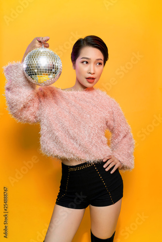Portrait of charming young female showing tongue and fooling around holding mirror ball on head posing on yellow background. Party and glitter fashion concept - 254888767