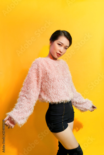 Short-haired girl in fashionable dancing. Young playful female model in stylish fur outfit. Beautiful happy woman having fun dance in studio on yellow - 254889389