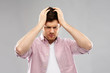 mind, health problem and stress concept - unhappy indian man suffering from headache over grey background