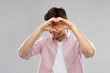 Leinwanddruck Bild - love, charity and valentine's day concept - smiling man making hand heart gesture over grey background