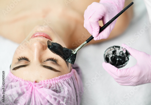Leinwanddruck Bild Doctor-cosmetologist applies with a brush a dark color special coating on patient's face for a cosmetic procedure