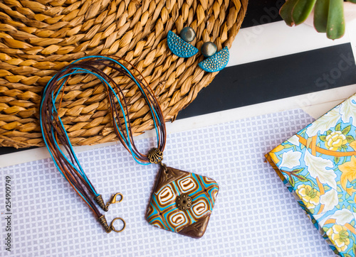 Jewelry flat lay with necklace boho style, earrings and notebook. Fashion background.