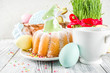 Leinwandbild Motiv Easter table setting concept, festive table with decoration of young grass, cake, pastel colored eggs, homemade cookies in shape of eggs, bunny rabbits. On a wooden background, copy space
