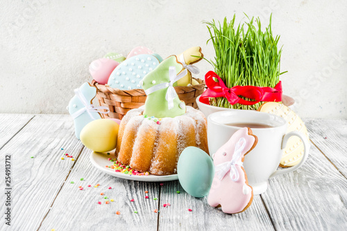 Easter table setting concept, festive table with decoration of young grass, cake, pastel colored eggs, homemade cookies in shape of eggs, bunny rabbits. On a wooden background, copy space