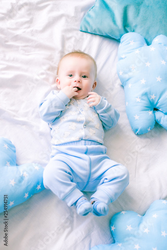 Cute toddler boy on bed at home surrounded by blue pillows