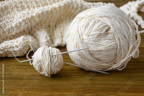 Ball of beige yarn by wool and knitting needles at home on brown wooden table