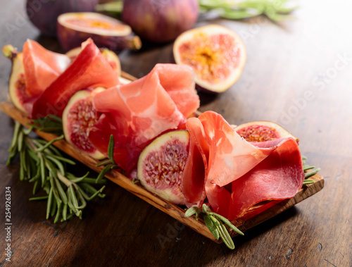 Prosciutto with figs and rosemary on a old wooden table. - 254926334