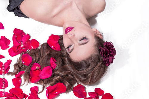 Leinwanddruck Bild beautiful young woman lying in bed with rose petals.