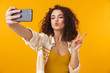 Leinwanddruck Bild - Image of positive woman 20s with curly hair smiling and taking selfie photo on smartphone