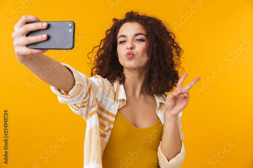 Leinwanddruck Bild Image of positive woman 20s with curly hair smiling and taking selfie photo on smartphone