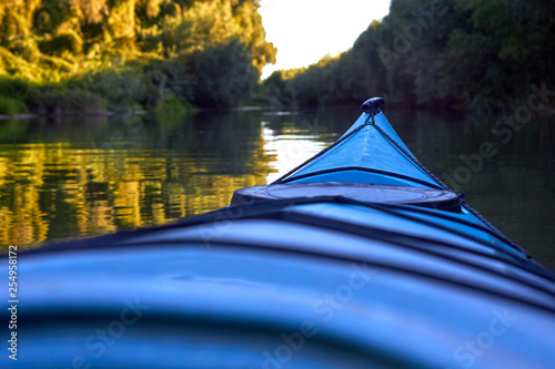 Bow (prow) of blue kayak against a background of green summer trees illuminated by the rays of the setting sun at the shore of Danube river. Kayaking on peaceful calm lake or river
