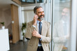 Handsome mature businessman with mobile phone in the office