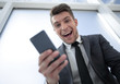happy businessman with phone looking at camera