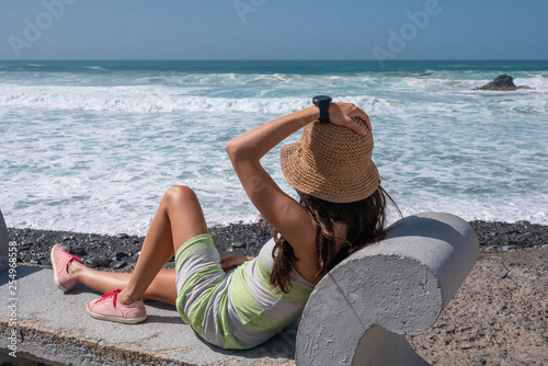 girl on a bench looking at the sea