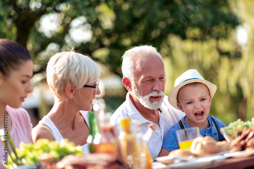 Happy family having a barbecue in summer - 254977516