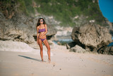 Slender sexy tanned girl in swimsuit posing on beach with sand and large stones