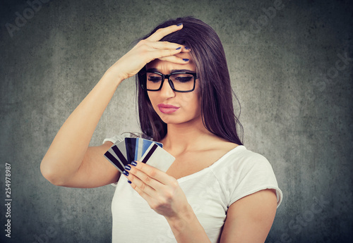 Leinwandbild Motiv stressed woman looking at too many credit cards full of debt
