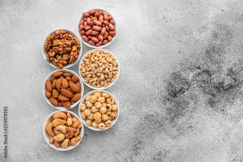 obraz lub plakat Assortment of nuts in white saucers on a concrete background. Food mix background, top view, copy space, banner