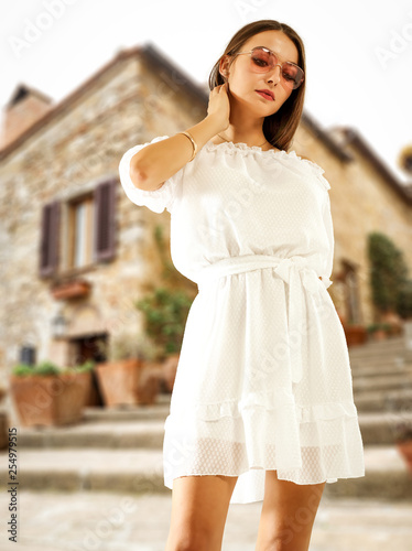 Slim young woman in summer dress and blurred background of city in Italy.