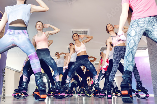 Bottom view of women doing exercises with dumbbells while wearing kangoo jumps footwear. Fitness studio interior.