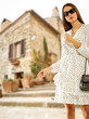 Leinwanddruck Bild - Slim young woman in summer dress and blurred background of city in Italy.