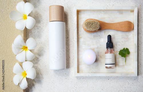 Leinwanddruck Bild Face cream, serum, lotion, moisturizer and face oil among white frangipani in the bath