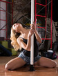 Young woman in denim shorts practicing pole dancing