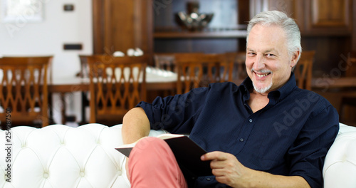 Mature man relaxing while reading a book on a sofa at home