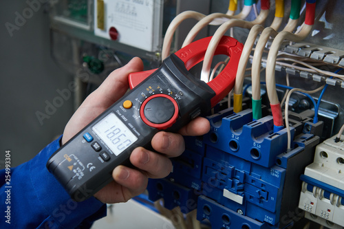Electrician work concept. Hand with multimeter tester in switchbox - 254993304