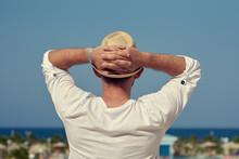 "Постер, картина, фотообои ""Attractive European man in sunhat is observing wonderful hotel's view."""