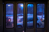 windows in the trolleybus in the door, view of the evening city cars on the road