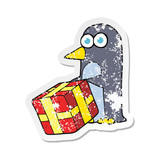 retro distressed sticker of a cartoon penguin with christmas present