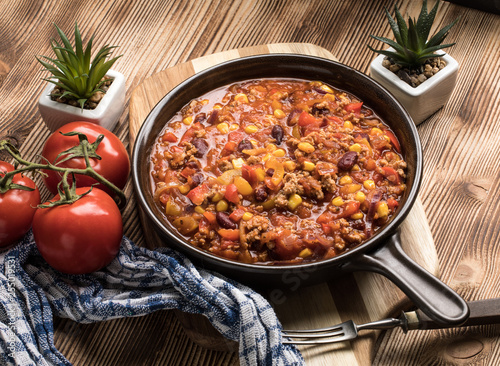 Chili con carne in a clay pan. - 255019531