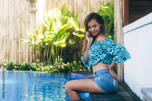 Sensual sexy girl in denim shorts and top sits on pool. Young tanned model resting on summer day