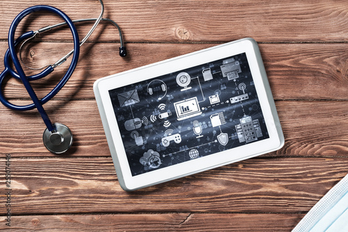 Concept of modern medicine with tablet on wooden table from top view