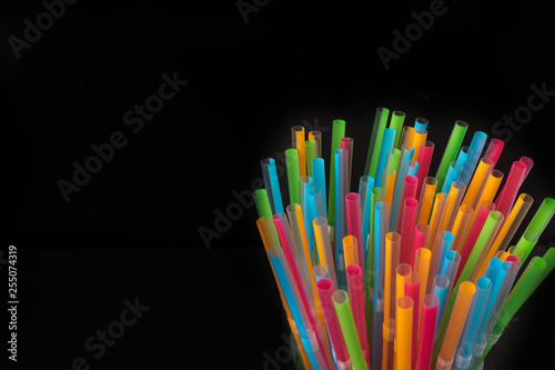 Plastic colorful straws. Celebration party background in black with space for copy text - 255074319