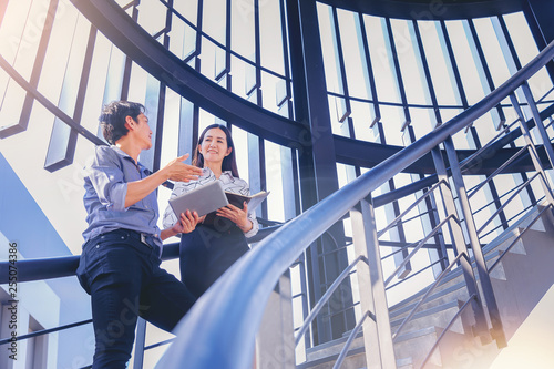 Two business colleagues get discussion at stairway in modern office using tablet
