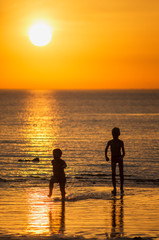 Children play in the sea at sunset. © Eugene