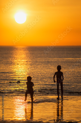 Children play in the sea at sunset.