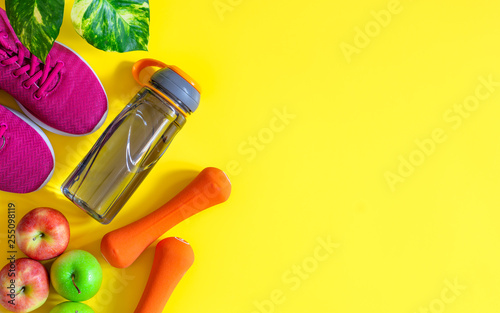 Leinwanddruck Bild Red and green apples, bottle of water, orange dumbbells and red sport shoes on yellow background. Fitness active healthy lifestyle concept background.