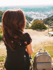 Girl with long hair photographed from behind, sitting on a hill and looking at the panorama of Los Angeles in the summer © KseniaJoyg