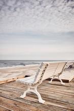"""Постер, картина, фотообои """"Empty bench on the beachfront, color toned picture."""""""