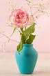 Delicate mini pink rose in a vintage blue vase on a tablein front of pink backgroud