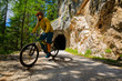 Leinwanddruck Bild - Single mountain bike rider on electric bike, e-mountainbike rides up mountain trail. Man riding on bike in Dolomites mountains landscape. Cycling e-mtb enduro trail track. Outdoor sport activity.