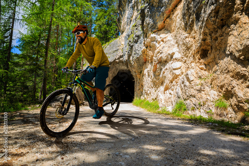 Leinwanddruck Bild Single mountain bike rider on electric bike, e-mountainbike rides up mountain trail. Man riding on bike in Dolomites mountains landscape. Cycling e-mtb enduro trail track. Outdoor sport activity.