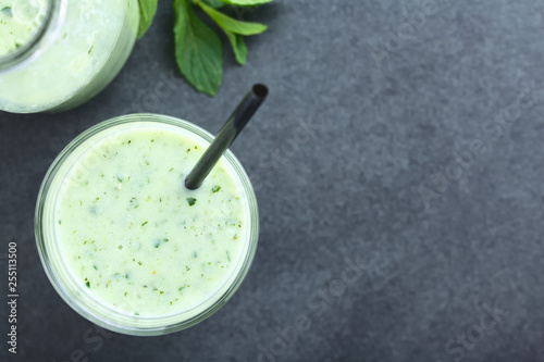 Refreshing green cucumber, yogurt, mint and lemon smoothie in glass, photographed overhead on slate (Selective Focus, Focus on the drink) © Ildi