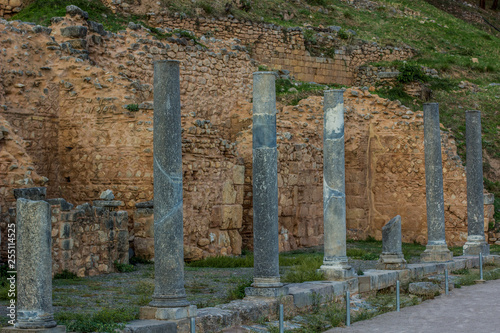 ruined stone pillars architecture object alley way from ancient Greece times touristic world heritage site
