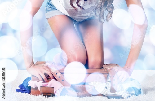 Leinwandbild Motiv Young  woman packing suitcase on background